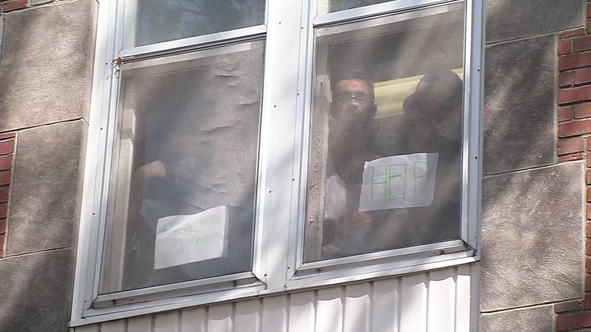 Residents of Dismass Charaties - St. Ann's halfway house hold up signs asking for help
