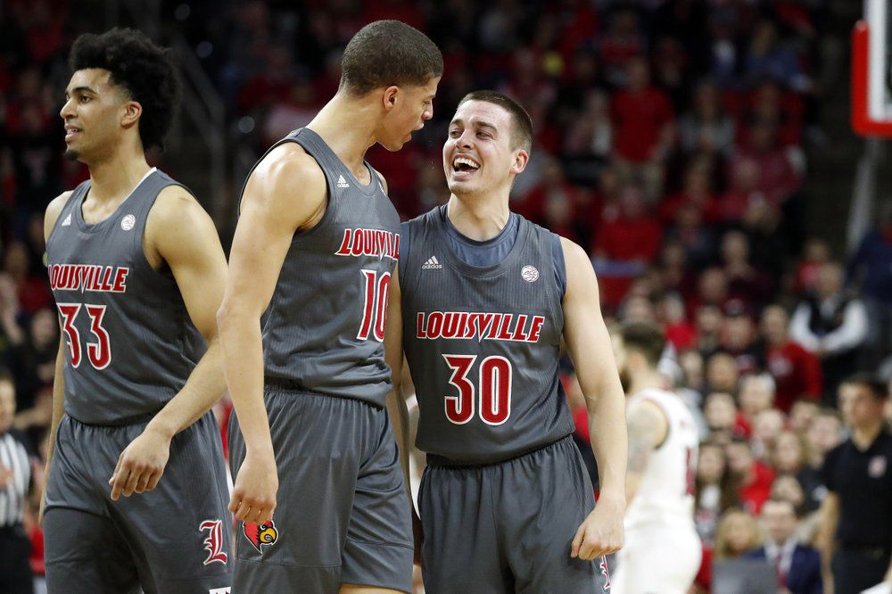 Louisville's Ryan McMahon (30) celebrates one of his 3-point shots with teammate Samuell Williamson