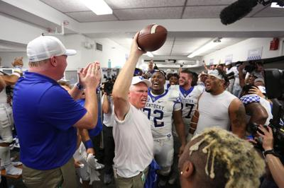 Kentucky football coach John Schlarman holds up the game ball after the Wildcats beat Tennessee
