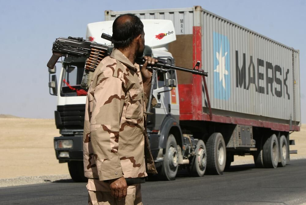 Private security contractor watches NATO supply truck