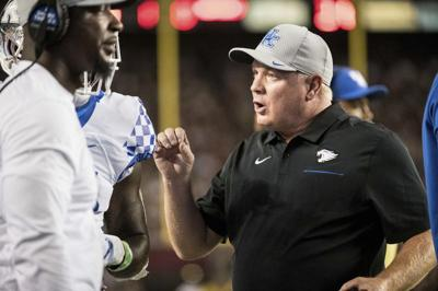 Kentucky head coach Mark Stoops talks with a player on the sideline