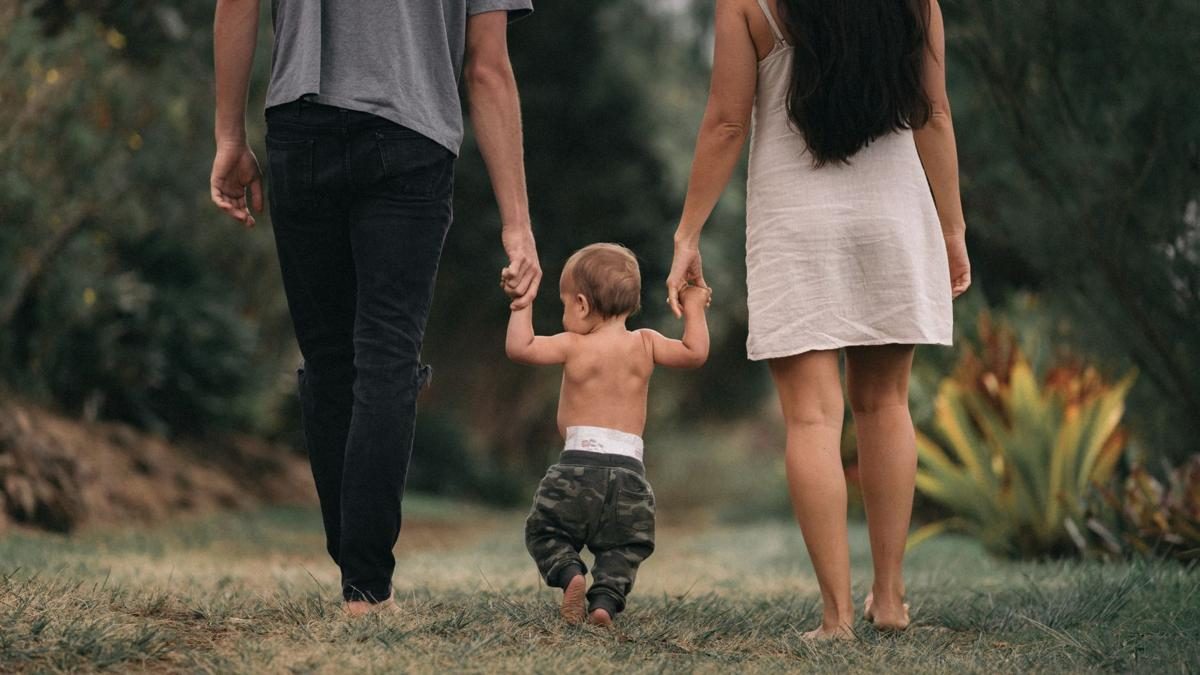 Parents walk hand-in-hand with toddler