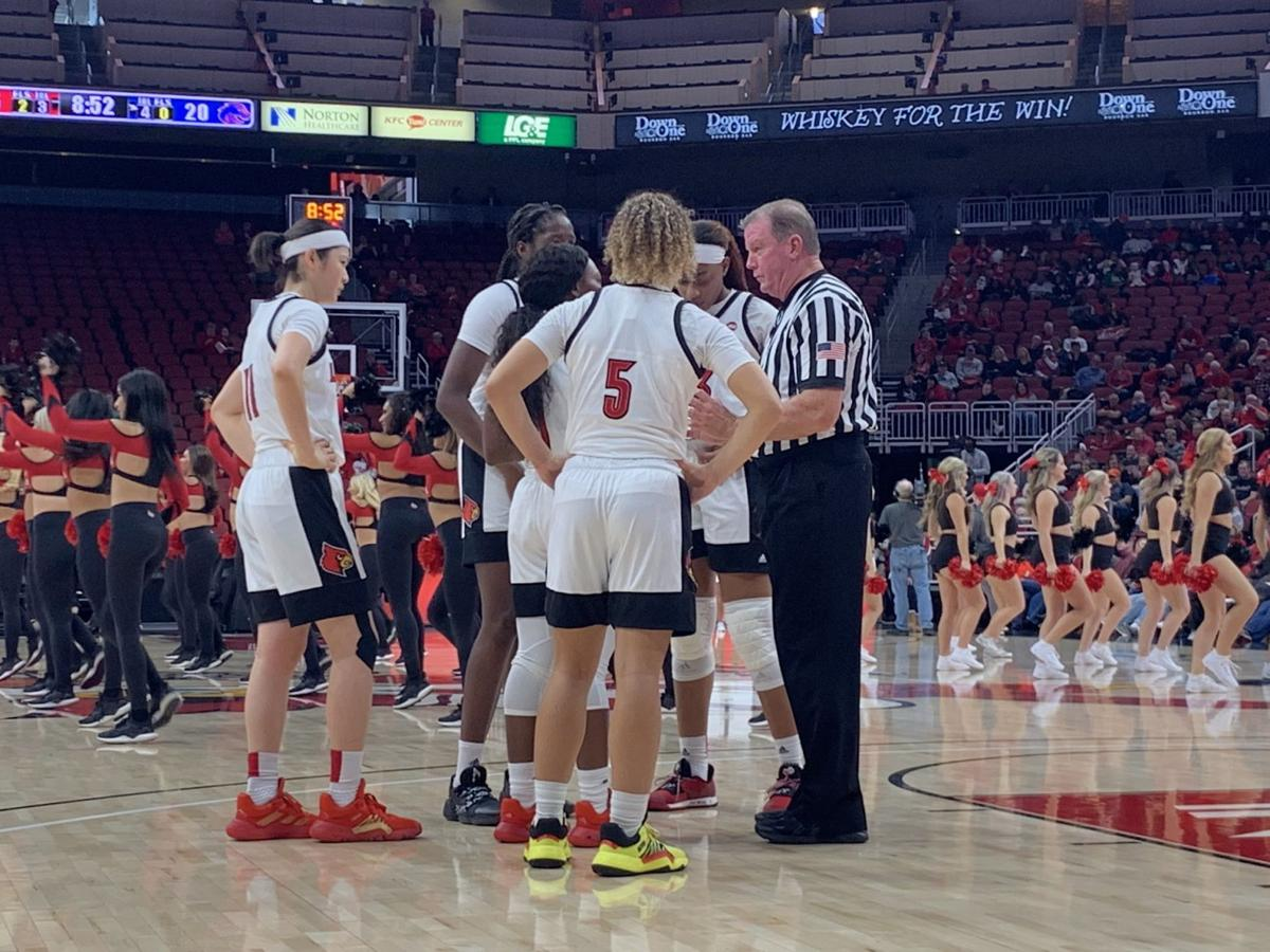 Members of the U of L women's basketball team talk with an official
