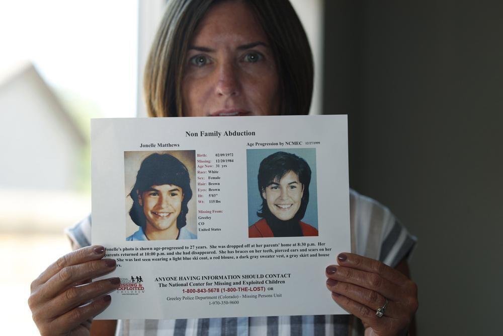 Jennifer Mogensen holds poster of adopted sister