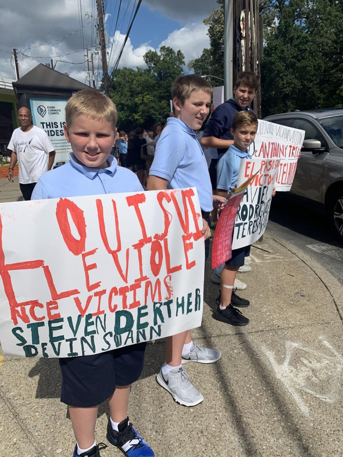 Saint Francis of Assisi students hold signs at anti-violence walk