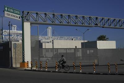 Man rides bike past international border bridge