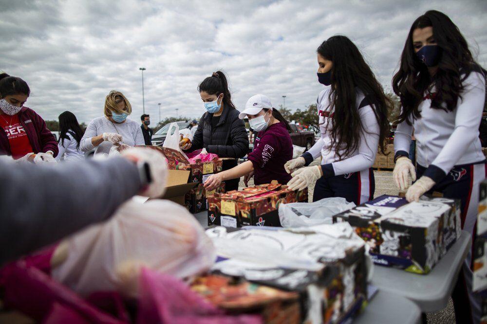 Texans Cheerleaders and other volunteers pack food AP.jpeg