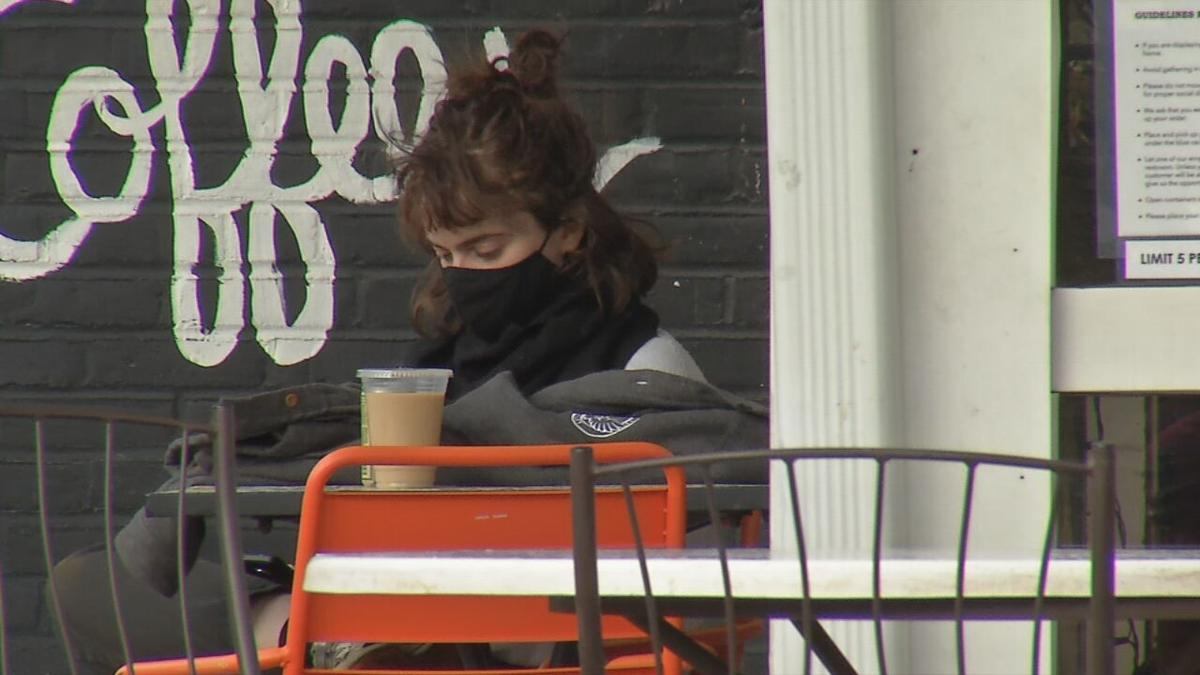 Customer gets coffee to-go and sits outside Safai Coffee while indoor seating is closed
