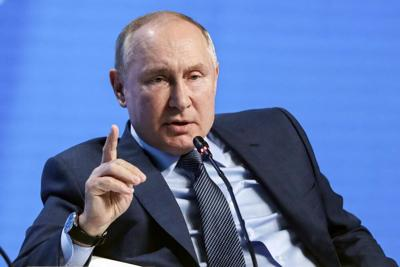 Putin gestures while seated
