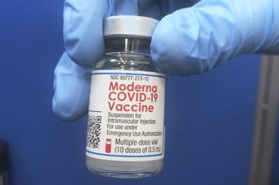 Vial of Moderna COVID-19 vaccine being held.jpeg