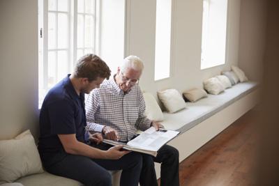 Senior man sitting looking at photo album  with male nurse