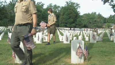 Boy Scouts put flags on headstones for Memorial Day