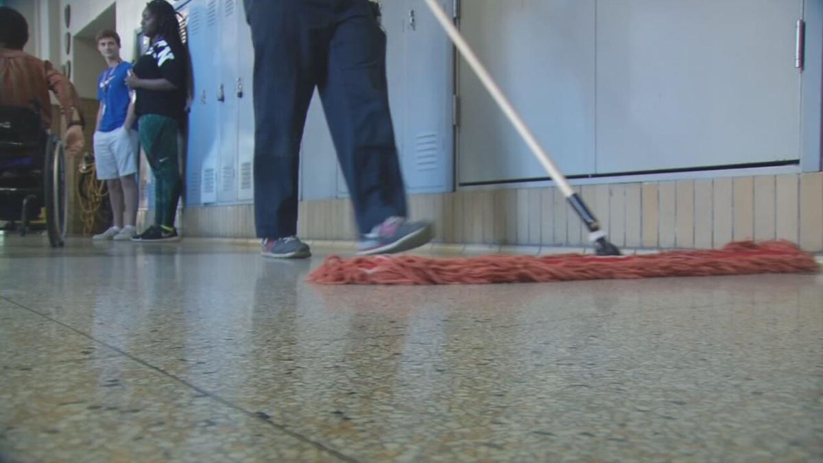 Custodian cleaning a school hallway (generic)