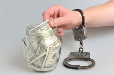 Handcuffed hand reaching into money jar