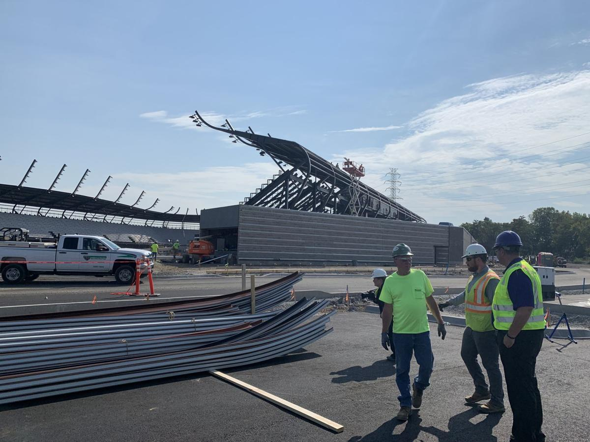 Crews shape the panels for the roof at Lynn Family Stadium
