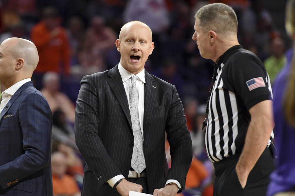 Louisville head coach Chris Mack, left, speaks with an official