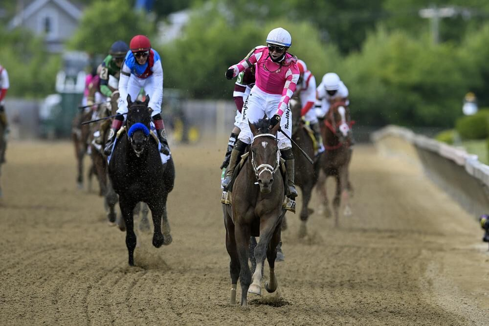 Flavien Prat atop Rombauer, center, reacts after winning the Preakness Stakes