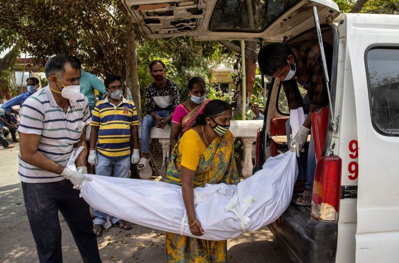 Relatives carry the body of a person, who died due to the coronavirus disease (COVID-19), for cremation at a crematorium ground in New Delhi