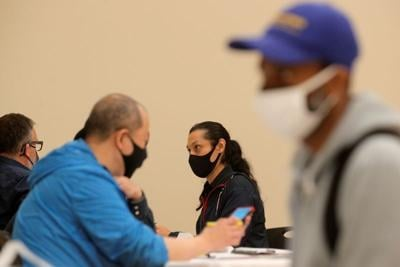 Applicants talk with recruiters during a restaurant job career fair in New York