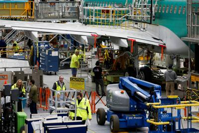FILE PHOTO: Employees work on several 737 Max aircrafts at the Boeing factory in Renton