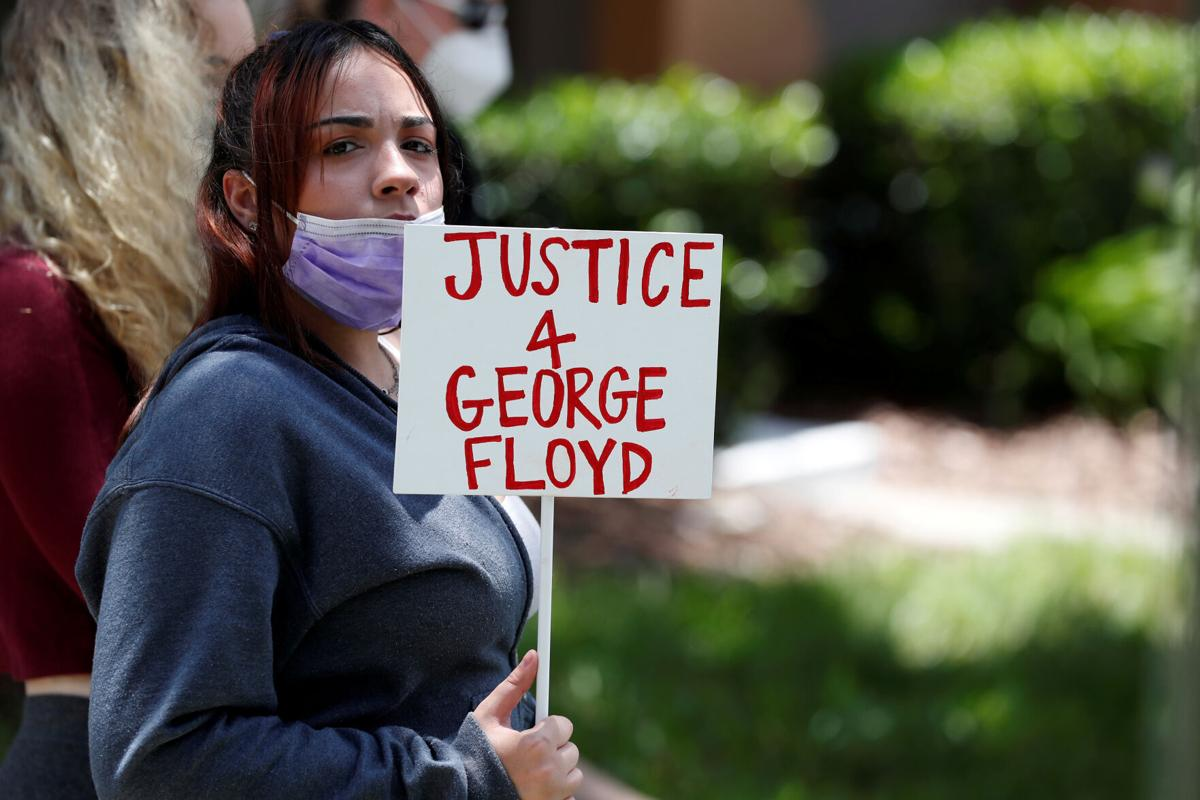 FILE PHOTO: A protester holds a sign outside the Florida home of former Minneapolis police officer Derek Chauvin, in Orlando