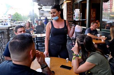 FILE PHOTO: Server Timi Sanchez waits on customers at Hennessey's Tavern as restaurants are opening for business on sidewalks as restrictions to prevent the spread of coronavirus disease (COVID-19) are eased in Las Vegas