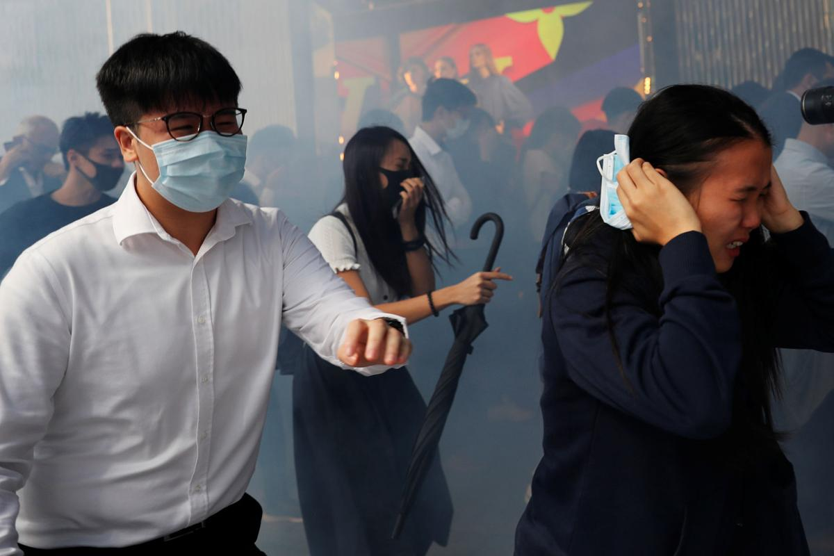 Office workers run away from tear gas as they attend a flash mob anti-government protest at the financial Central district in Hong Kong