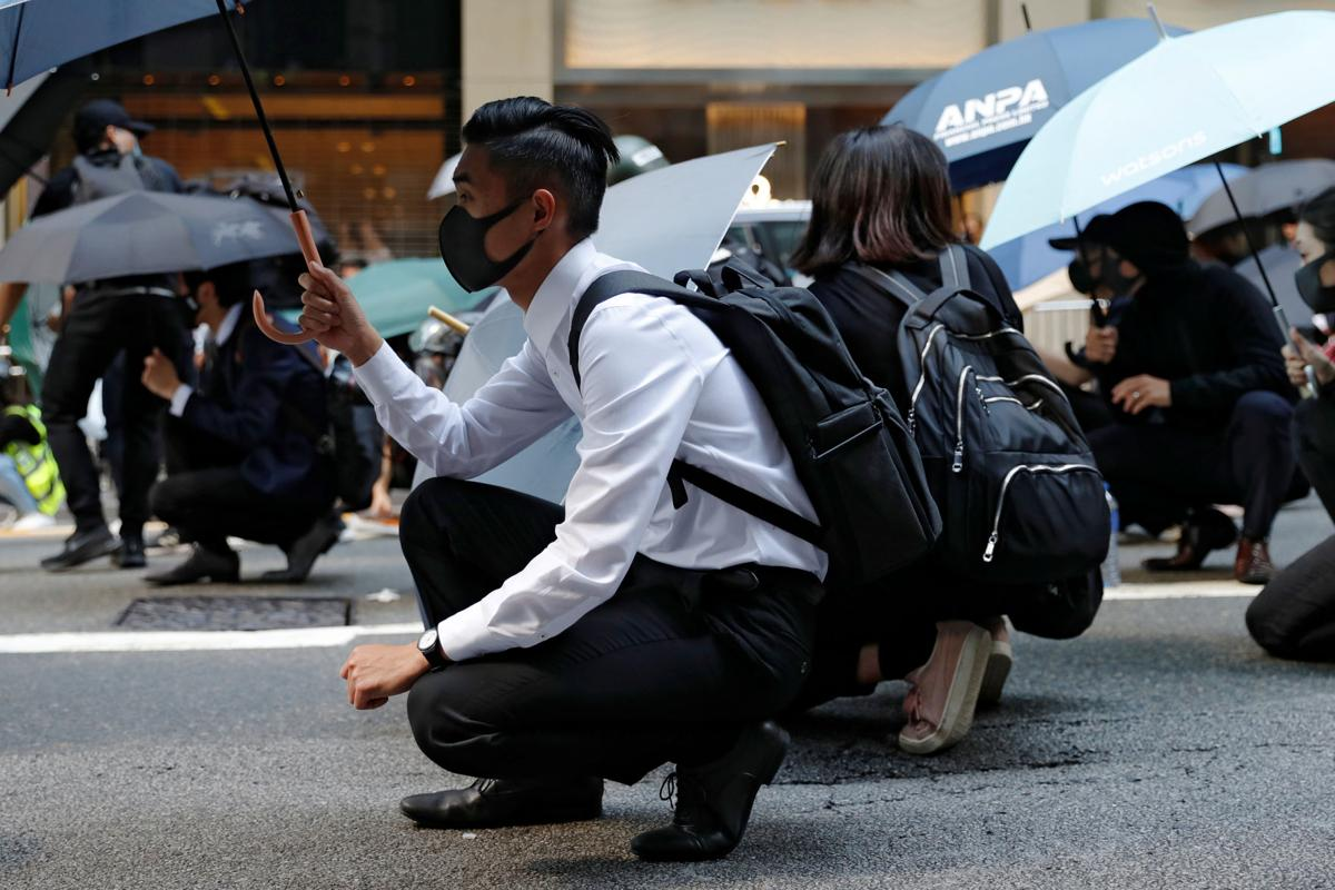 Office workers hold umbrellas as they attend a flash mob anti-government protest after police fired tear gas at the financial Central district in Hong Kong