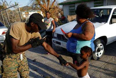 A volunteer of the NGO World Central Kitchen bumps fists with a girl during a food distribution operation, after Hurricane Dorian hit the Abaco Islands in Spring City