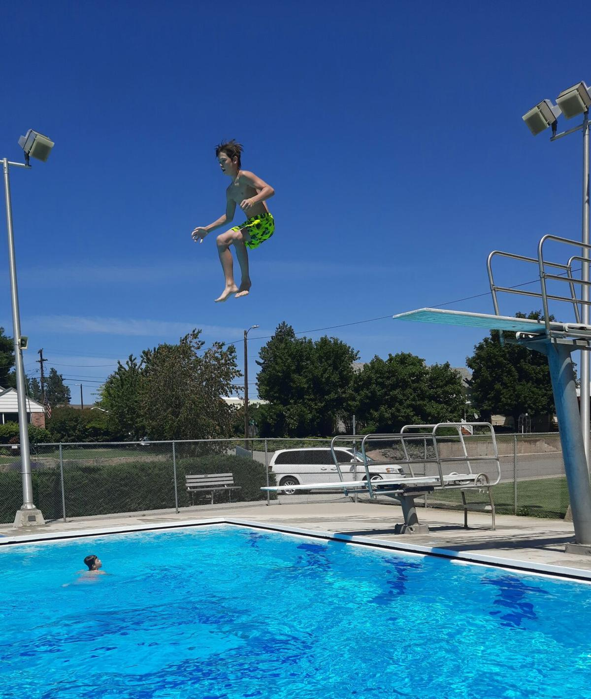 Wyatt Williams leaps from the high dive, enjoying the reopening of the Waterville Pool.jpg