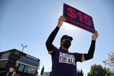 FILE PHOTO: A man holds a minimum wage sign at a rally in California