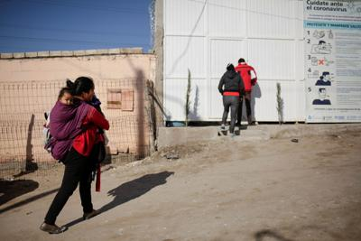 A migrant from Central America, asylum seeker under the Migrant Protection Protocols (MPP) program, carries her son outside the El Buen Pastor shelter in Ciudad Juarez