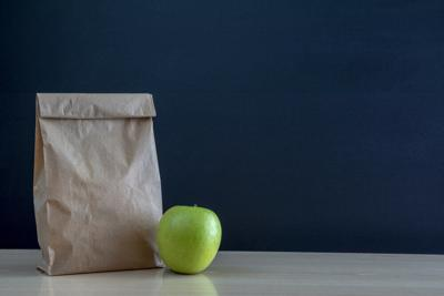 Brown paper bag and  a green on blackboard background.