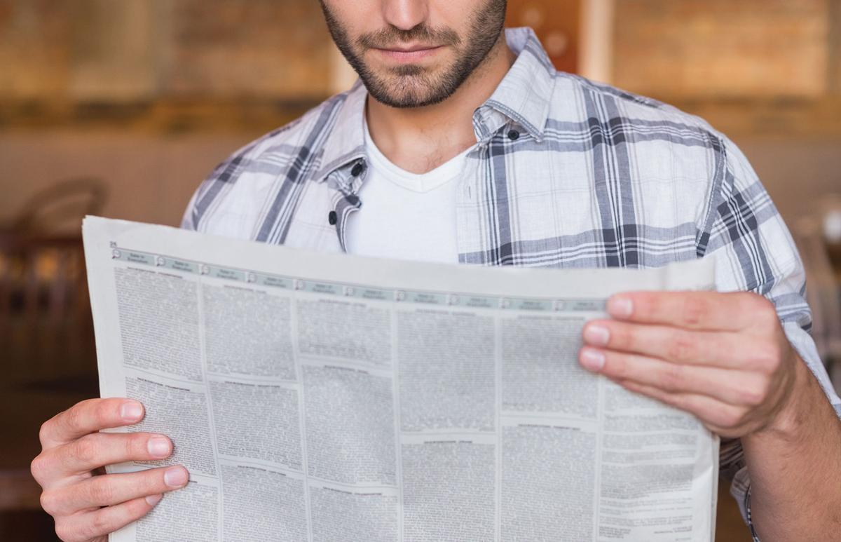 student holding newspaper