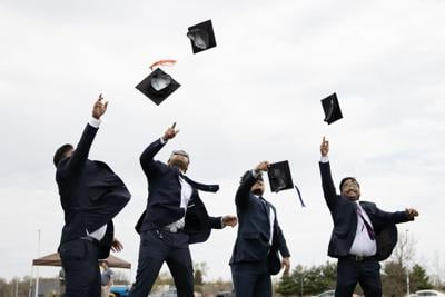 A group of graduates throw their caps in the air on the lawn outside of Floyd Hall.