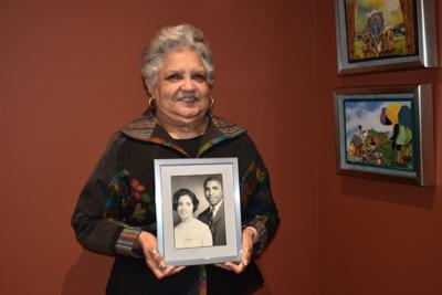 Goergella Miller poses with a photo of her and her husband.