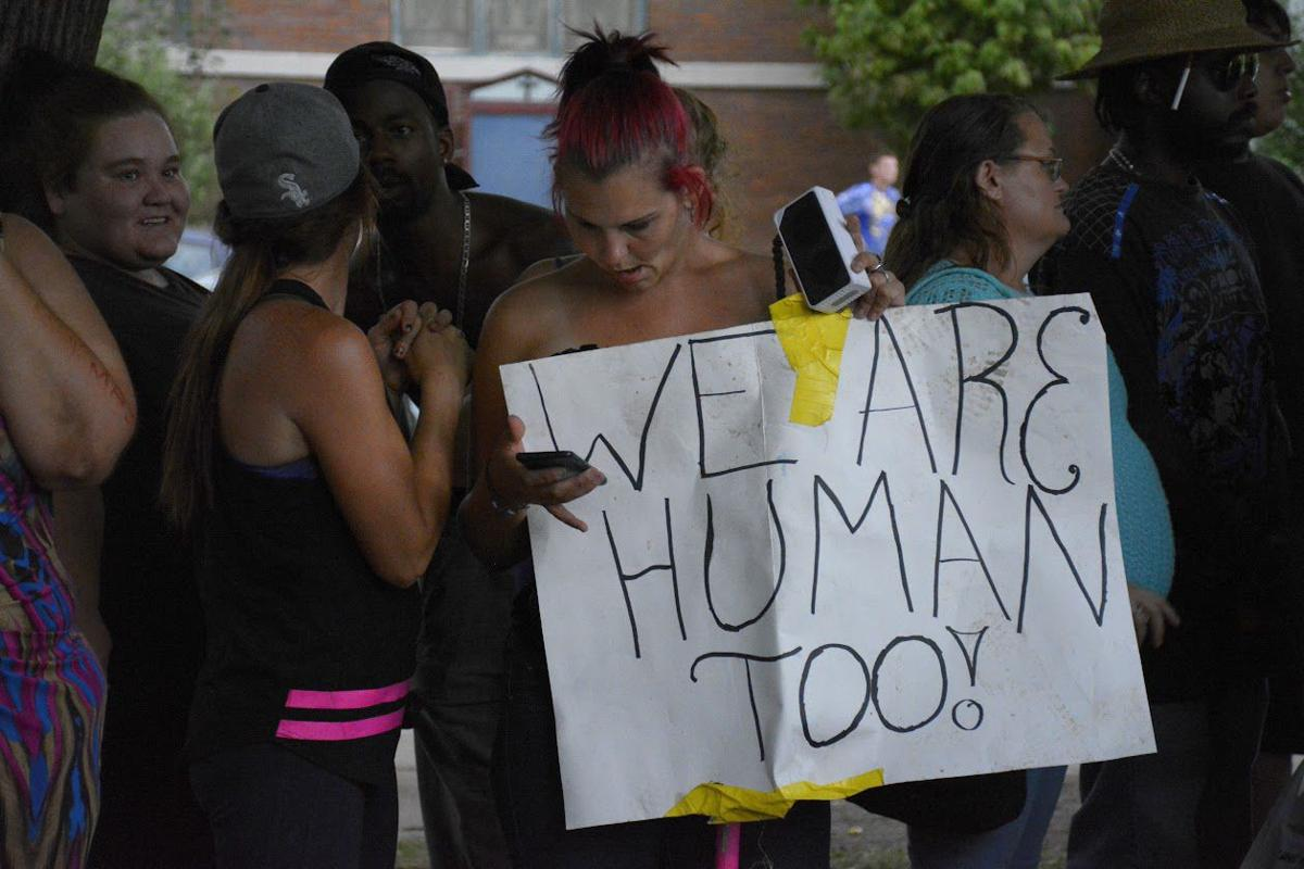 """""""We are human too,"""" a sign reads."""