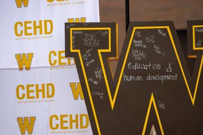 Graduates signed a 'w' outside Floyd Hall.