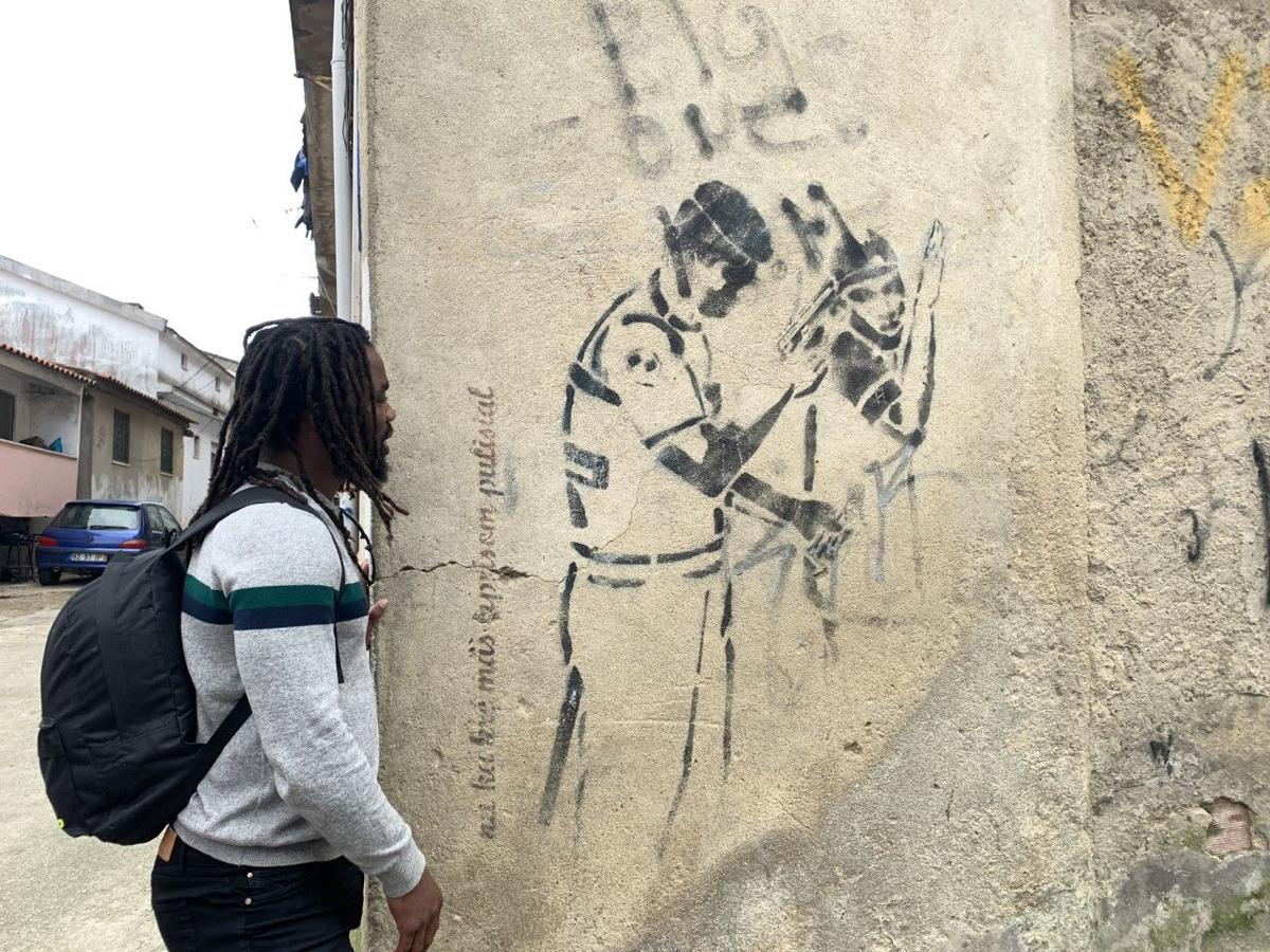The tour guide looks at a mural depicting the police brutality residents of Cova da Moura face.