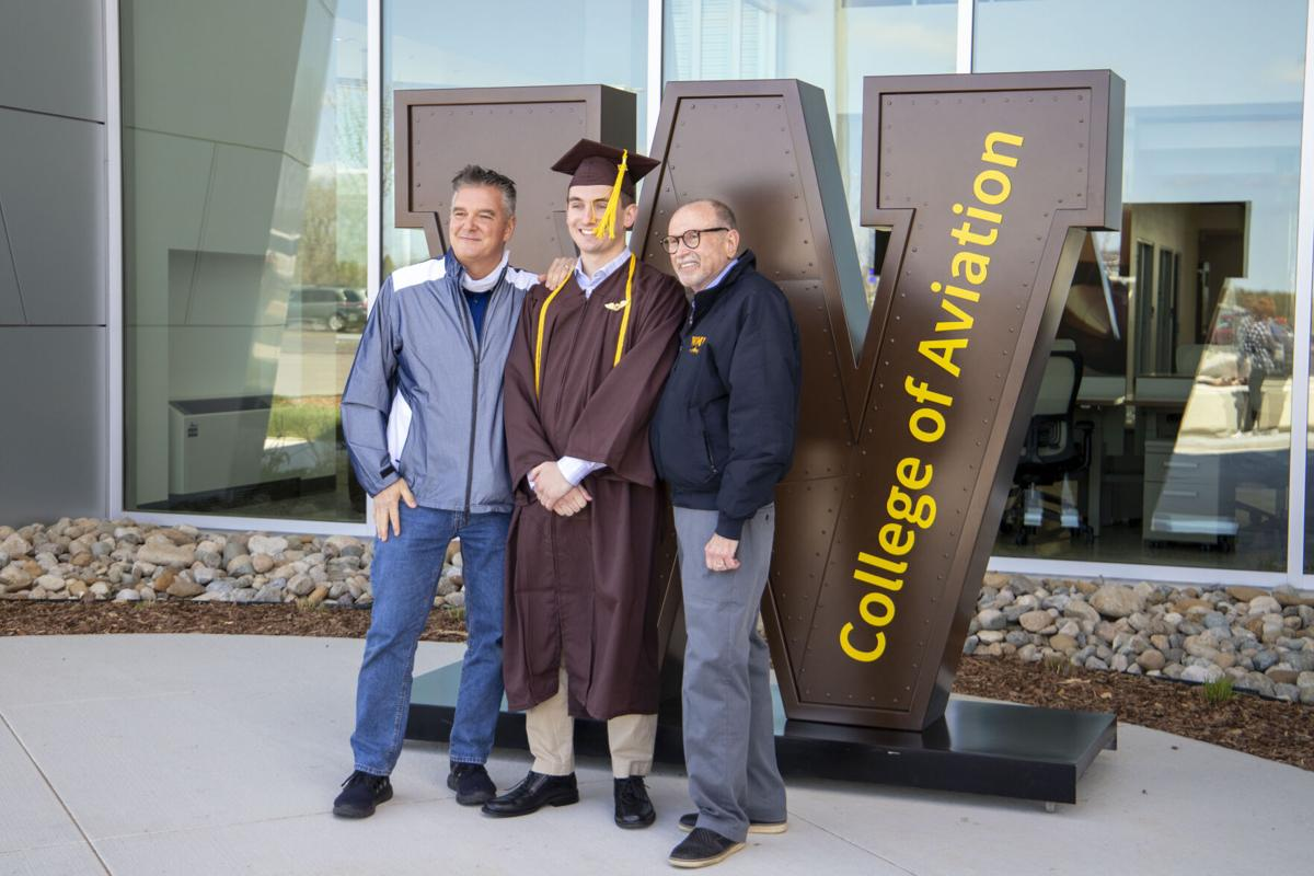 A WMU graduate and his father pose for a picture with College of Aviation Dean Captain Dave Powell.
