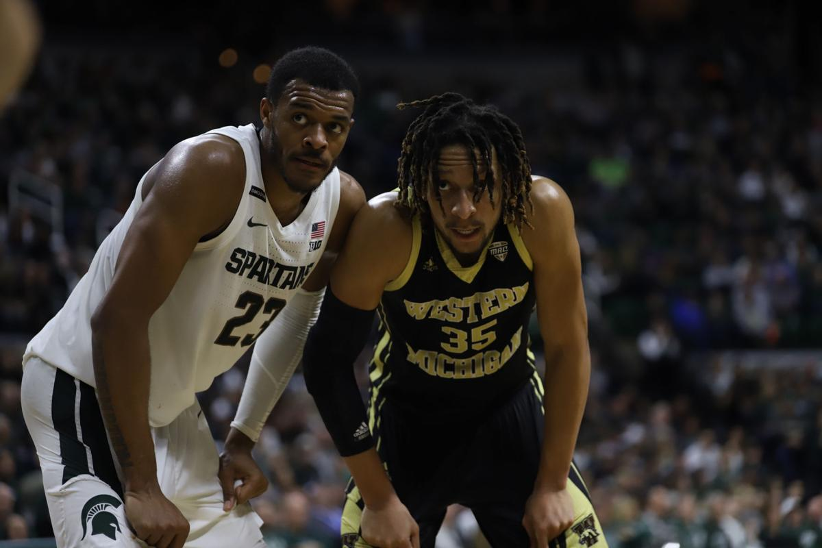 Michigan State's Xavier Tillman (23) and Western Michigan's Brandon Johnson (35) wait for the resume in action.