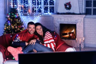 Couple watching TV at home during Christmas generic