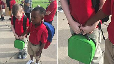 Boy holds hands of crying classmate with autism