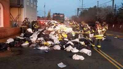 Firefighters extinguish trash fire in garbage truck