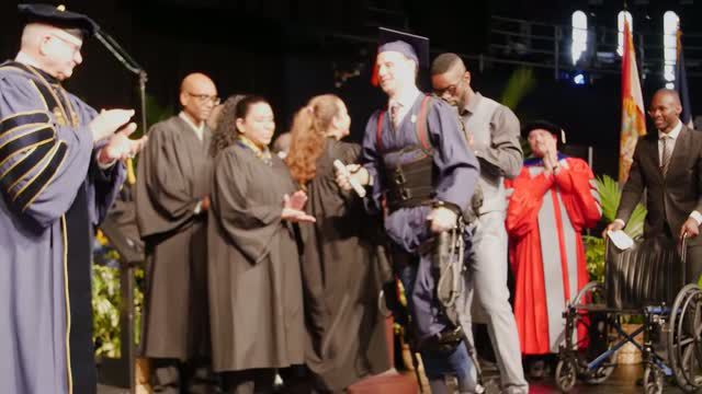 College student who uses wheelchair walks across stage to receive diploma