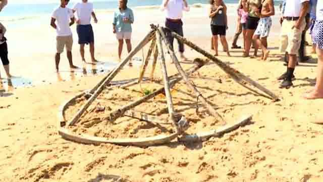 Large metallic object puzzling beachgoers removed from water