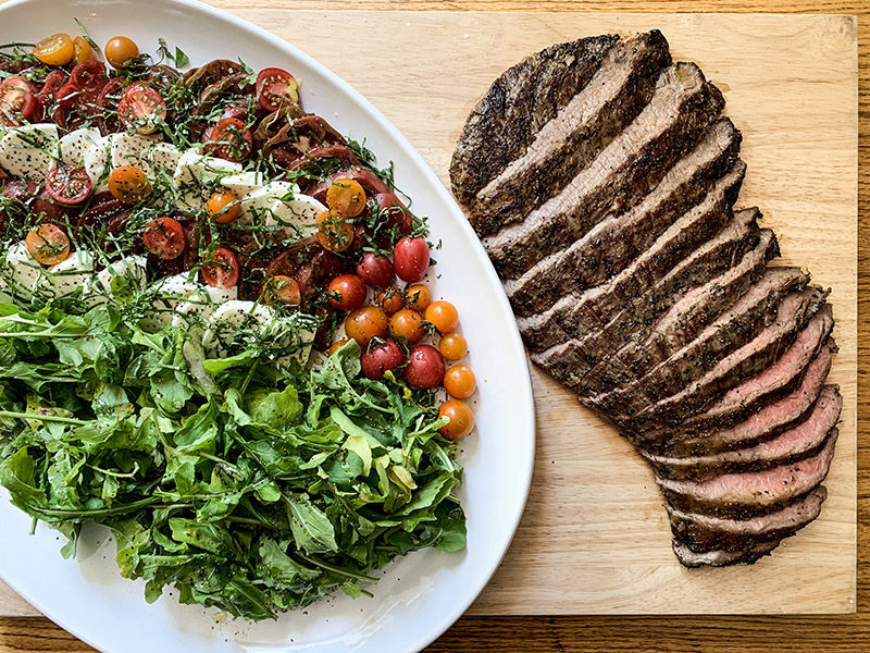 Grilled flank steak with heirloom tomatoes, arugula and mozzarella