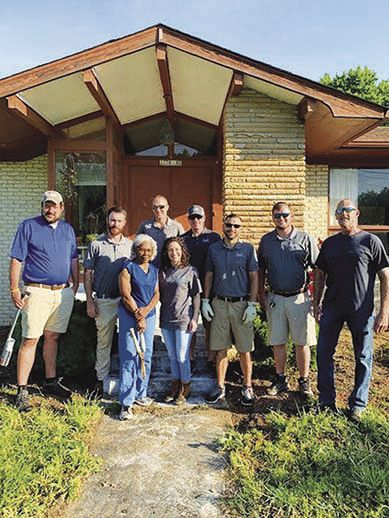Submitted Members of the Goodall Homes team, which partnered with Habitat for Humanity's Critical Repair Program to make some long overdo critical repairs on Mary Hunter's home, stand with Mary Hunter in front of her newly repaired home.