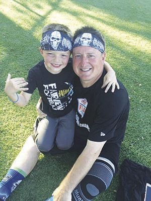 Chris Hughes takes a moment to pose for a photo with his son Cade last month after helping guide the Mean Machine, a flag football team, to the regional championship in Nashville.