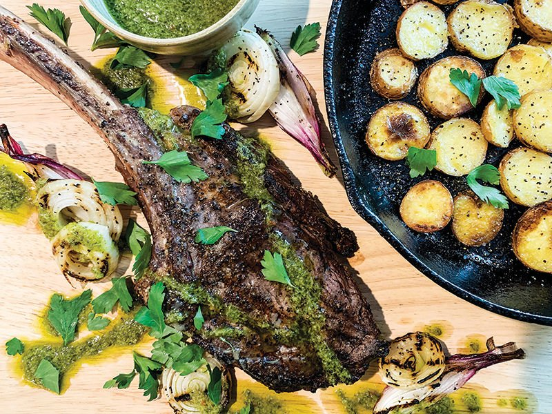Grilled Tomahawk steak with roasted potatoes, onions and parsley sauce